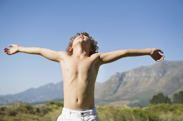 Shirtless little boy standing with his eyes closed and arms outstretched against mountain
