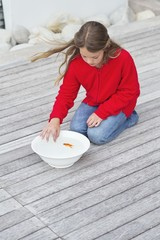 Girl touching a fish in a bowl