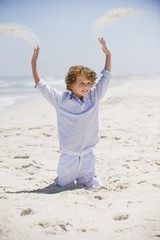 Boy playing in sand with his arms raised