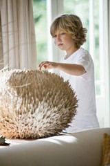 Boy touching a round shape object at home