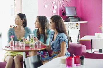 Three women looking away while eating food in a restaurant