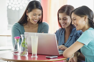 Three women using laptop in a restaurant