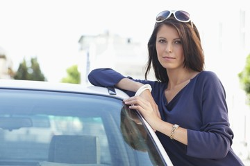 Portrait of a beautiful woman leaning on a car