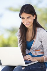 Portrait of a woman using a laptop and smiling