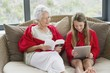 Senior woman reading a magazine with her granddaughter using a digital tablet