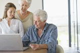 Senior man doing home shopping with a credit card with his family near him