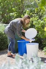 Woman throwing papers in garbage bin
