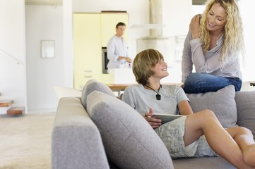 Teenage boy using a digital tablet and talking to his mother