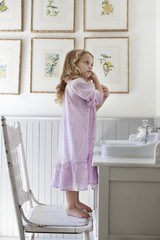 Cute little girl standing on a chair in front of a bathroom sink