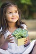 Cute little girl holding a potted plant and looking up