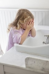 Cute little girl washing face in bathroom sink