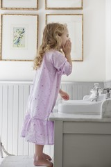 Cute little girl washing face in a bathroom