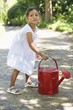 Cute little girl holding a watering can