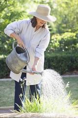 Senior woman in straw hat watering plants in a garden