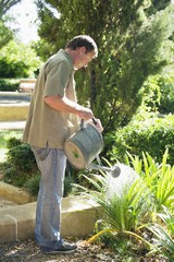 Side profile of a mature man watering plants in a garden