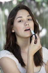 Portrait of a beautiful young woman applying lipstick
