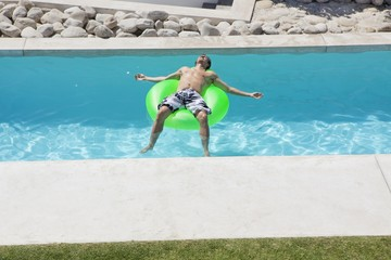 Man relaxing on an inflatable ring in a pool