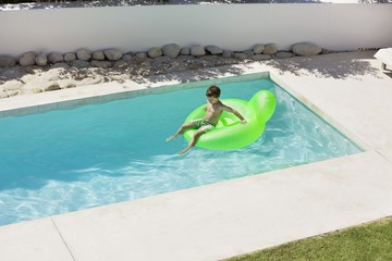 Boy sitting on inflatable ring in swimming pool