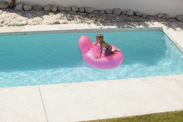 Boy playing on an inflatable ring in swimming pool