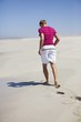 Rear view of a man walking on sand