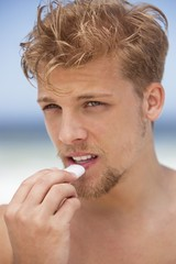 Young man applying moisturizer on his lips