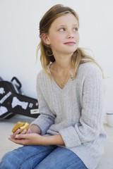 Side profile of a beautiful girl eating cookies