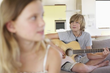 Teenage boy playing a guitar with his sister in foreground