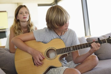 Teenage boy playing a guitar with her sister standing behind him listening