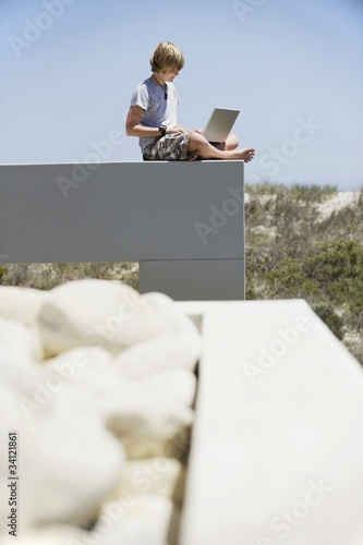 Teenage boy sitting at the edge of a terrace and using a laptop