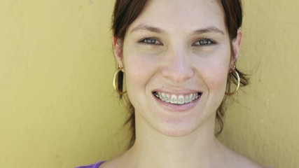 young woman with orthodontic braces smiling