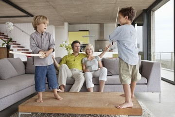 Boys playing with their parents sitting on a couch