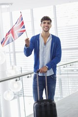 Portrait of a man holding British flag and a suitcase at an airport