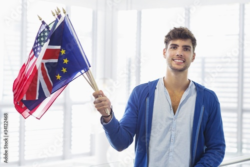 Portrait of a man holding flags of various countries at an airport