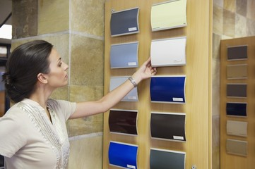 Young woman looking at color samples at car showroom