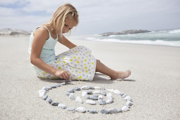 Girl arranging pebbles in spiral shape on the beach