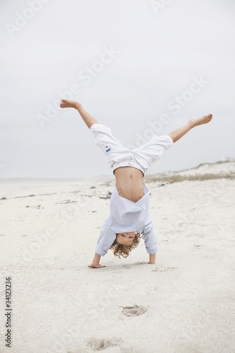 Boy doing handstand on beach