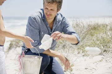 Mid adult man with his son cleaning the beach
