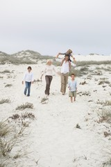 Couple walking on the beach with their children