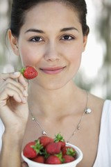 Portrait of a young woman holding a bowl of strawberries