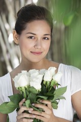 Portrait of a young woman holding bunch of white flowers