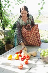 Mature woman collecting vegetables and fruits from the table