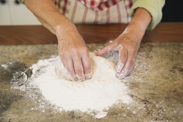 Close-up of a senior woman's hand mixing flour