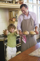 Little boy showing thumbs up sign with father holding baked breads