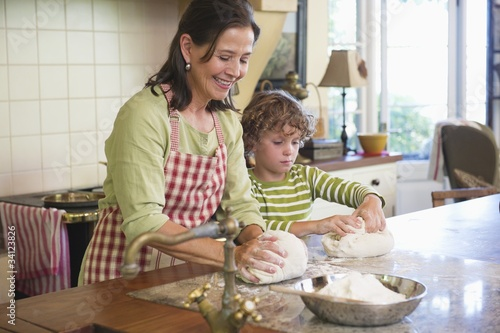 Grandmother and little boy kneading dough at kitchen