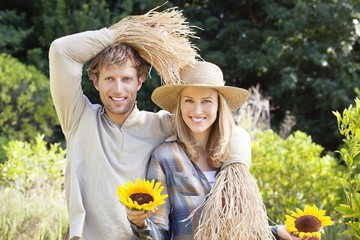 Portrait of a couple in scarecrow pose in a field