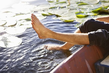 Man lying in a boat and dipping his legs in a pond