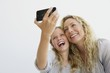Girl with her mother taking picture of themselves with a mobile phone