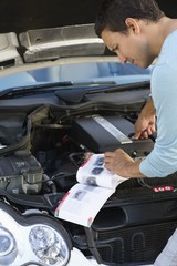 Mid adult man looking at broken car engine