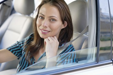 Portrait of a beautiful young woman sitting at driver's seat