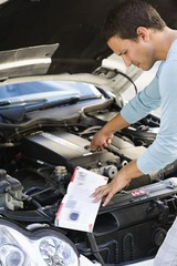 Mid adult man looking at broken car engine